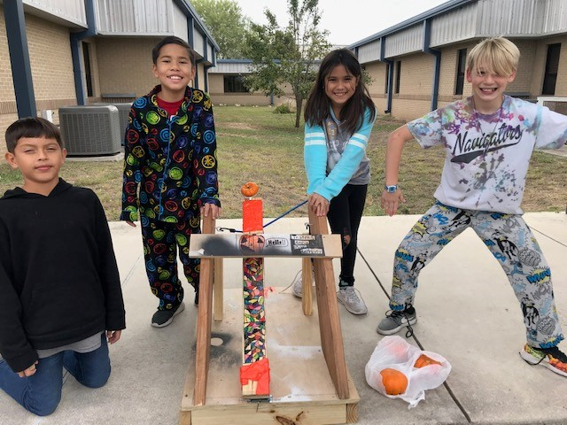 four students with catapult